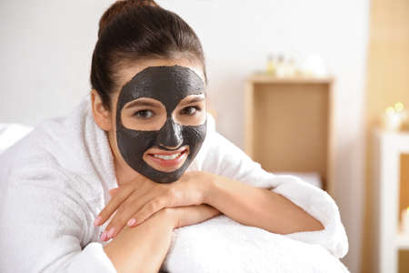 Beautiful woman with black mask on face relaxing in spa salon. Space for text