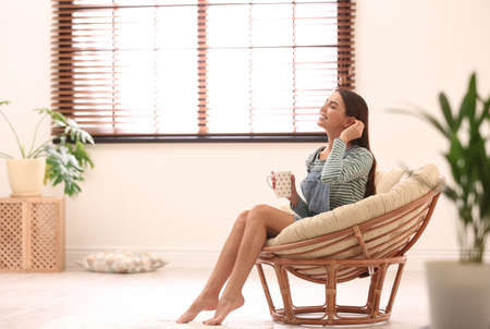 Young woman relaxing in papasan chair near window with blinds at home. Space for text Stock Photo