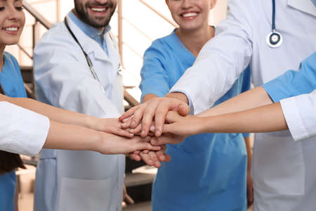 Team of medical doctors putting hands together indoors, closeup. Unity concept