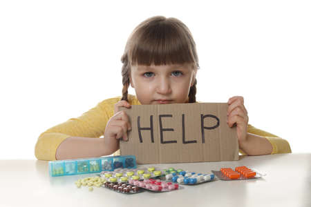 Crying little child with many different pills and word Help written on cardboard against white background. Danger of medicament intoxication 写真素材