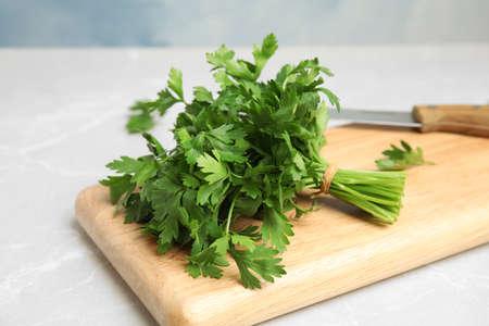 Wooden board with fresh green parsley on table, closeup Zdjęcie Seryjne
