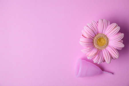 Flat lay composition with menstrual cup and gerbera flower on color background, space for text. Gynecological care Archivio Fotografico