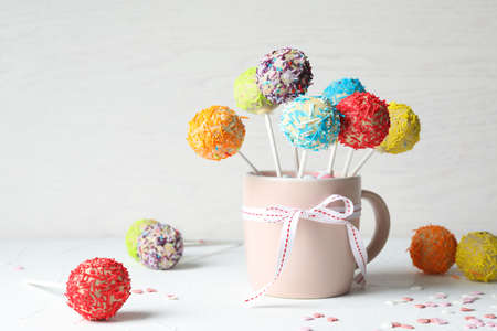 Cup with bow and yummy colorful cake pops on table. Space for text