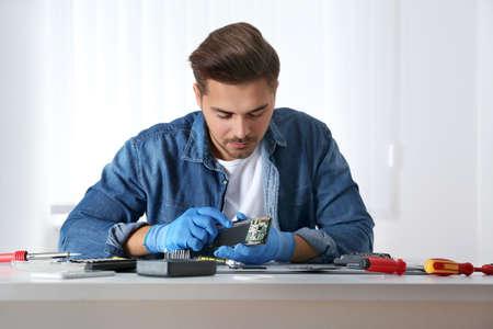 Technician repairing broken smartphone at table in workshop Stock Photo