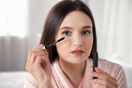Beautiful woman holding mascara brush with fallen eyelashes indoors