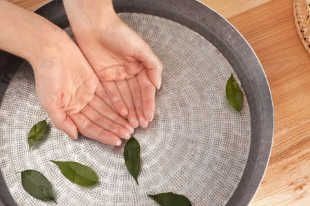 Woman soaking her hands in bowl with water and leaves on wooden table, top view. Spa treatment Stockfoto