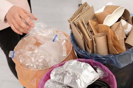 Woman putting used plastic bottle into trash bin, closeup. Waste recycling
