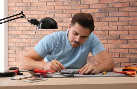 Technician repairing broken smartphone at table in workshop Reklamní fotografie
