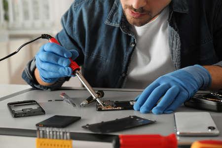 Technician repairing broken smartphone at table, closeup Standard-Bild