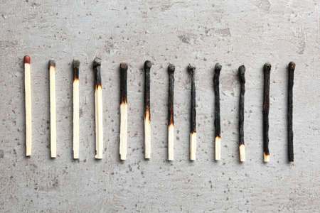 Row of burnt matches and whole one on grey background, flat lay. Human life phases concept