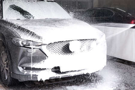Cleaning automobile with high pressure water jet at car wash