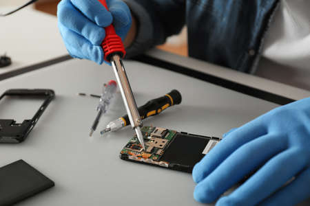 Technician repairing broken smartphone at table, closeup Standard-Bild