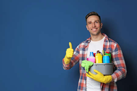 Man with basin of detergents on color background. Space for text Foto de archivo - 124547575