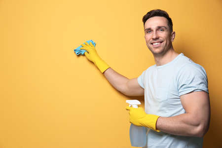 Man cleaning color wall with rag and sprayer. Space for text Foto de archivo - 124547576