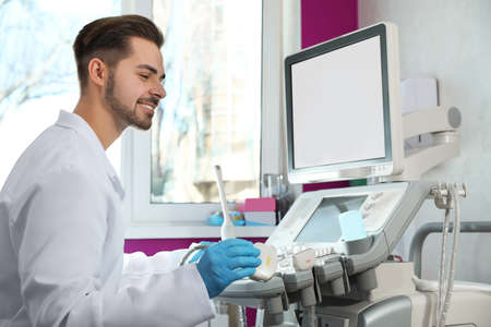 Ecografista con máquina de ultrasonido moderna en la clínica