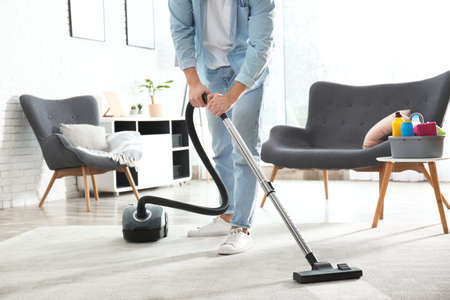 Janitor with vacuum cleaner in living room, closeup Foto de archivo