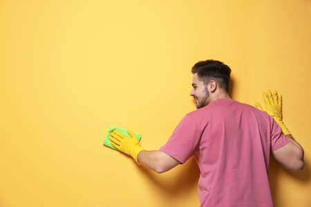 Man cleaning color wall with rag. Space for text Foto de archivo - 124547621