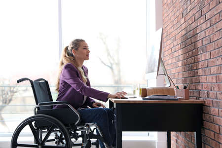 Woman in wheelchair working with computer at table indoors Stockfoto