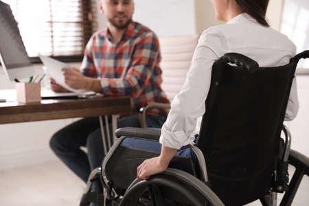 Mujer en silla de ruedas con su colega en el lugar de trabajo, primer plano