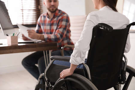 Woman in wheelchair with her colleague at workplace, closeup 免版税图像