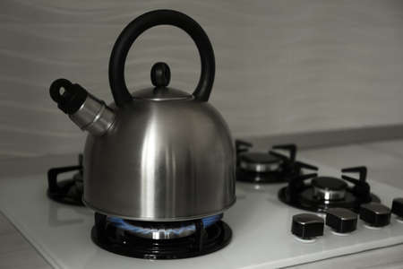 Steel kettle with whistle on modern gas stove. Space for text