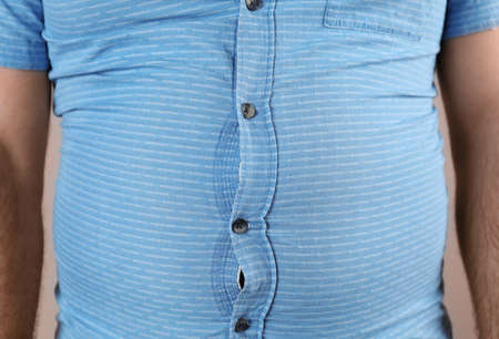 Overweight man with large belly in tight shirt , closeup