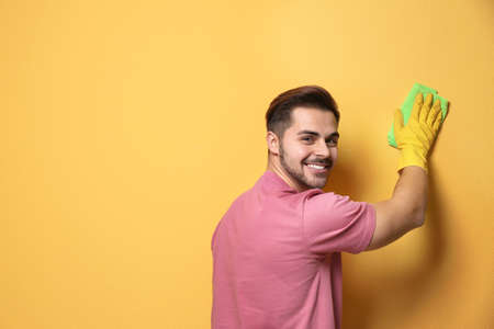 Man cleaning color wall with rag. Space for text Foto de archivo - 124548673