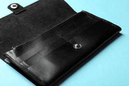 Open leather wallet on color background, closeup