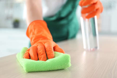 Worker in gloves cleaning table with rag, closeup. Space for text