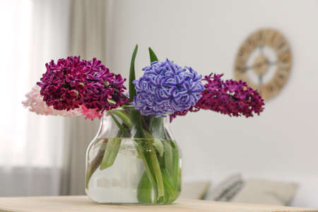 Beautiful hyacinths in glass vase on table indoors. Spring flowers 免版税图像