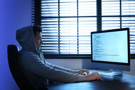 Man using computer in dark room. Criminal offence Imagens
