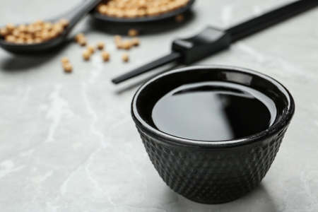 Bowl of soy sauce on grey table, closeup. Space for text Banque d'images