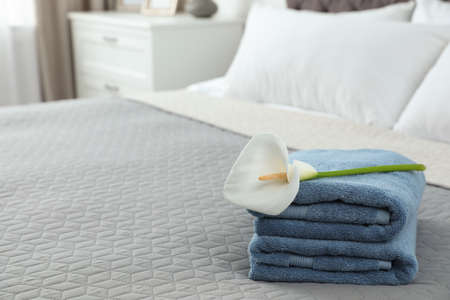 Stack of clean towels with flower on bed indoors. Space for text Imagens