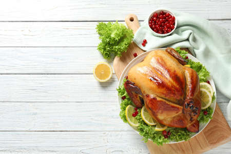Delicious roasted turkey on wooden table, top view. Space for text