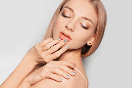 Beautiful young woman with shiny manicure on light background, closeup. Nail polish trends Фото со стока