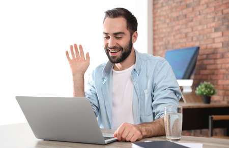 Young man using video chat on laptop in home office Banco de Imagens