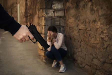 Armed man holding woman hostage outdoors, focus on hand with gun. Criminal offence Imagens
