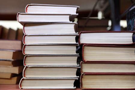 Pile di libri sullo scaffale in biblioteca