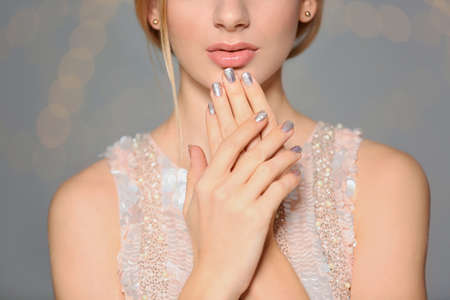 Beautiful young woman with shiny manicure on blurred background, closeup. Nail polish trends