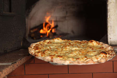 Taking tasty pizza out of oven in restaurant kitchen Imagens