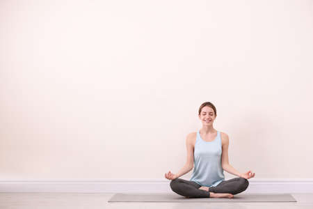 Young woman meditating near light wall, space for text. Zen concept