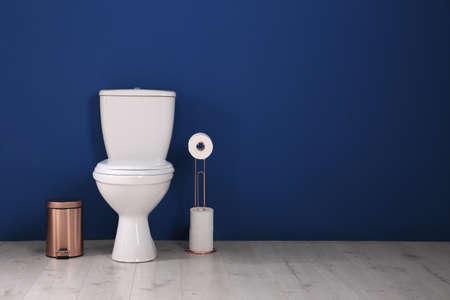 Interior de baño simple con inodoro nuevo cerca de la pared de color. Espacio para texto