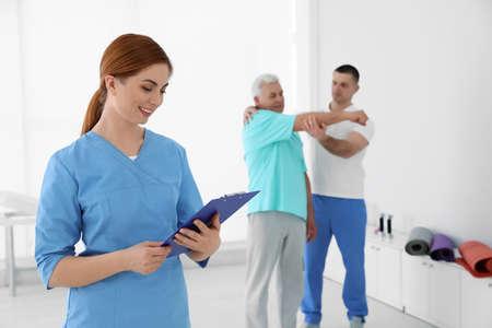 Retrato de fisioterapeuta profesional con portapapeles en centro de rehabilitación. Espacio para texto Foto de archivo