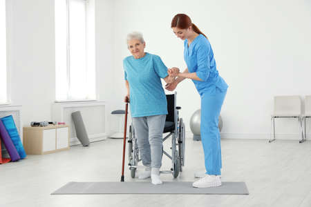 Professional physiotherapist working with elderly patient in rehabilitation center 版權商用圖片 - 124550250