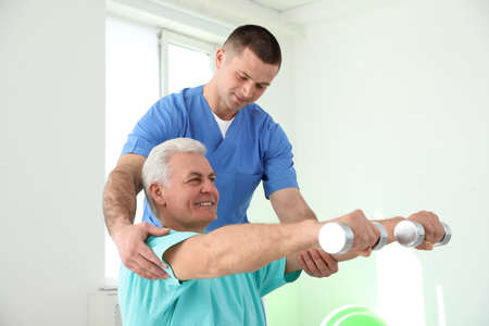 Professional physiotherapist working with senior patient in rehabilitation center Stock Photo