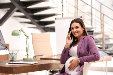 Young pregnant woman talking on phone while working in office