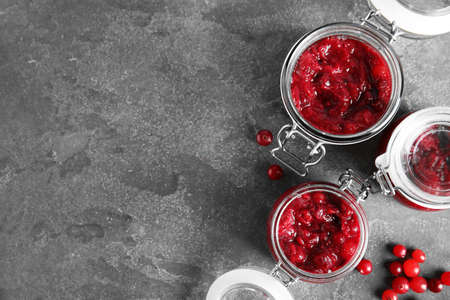 Jars with tasty cranberry sauce on grey background, flat lay. Space for text