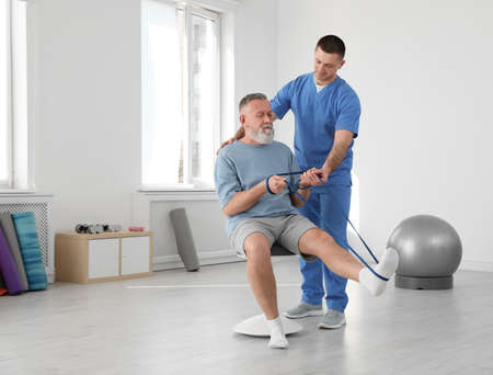 Professional physiotherapist working with senior patient in rehabilitation center 免版税图像