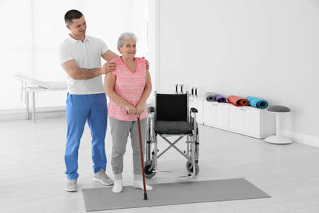 Professional physiotherapist working with elderly patient in rehabilitation center. Space for text