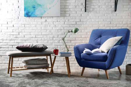 Room interior with comfortable furniture and books near brick wall Stock fotó